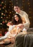 Jeunes couples embrassant dans les lumières et la décoration de Noël, habillées dans le blanc, arbre de sapin sur le fond en bois Photographie stock libre de droits