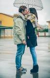 Jeunes couples embrassant dehors sous le parapluie dans a Photographie stock libre de droits