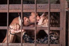 Jeunes couples embrassant derrière des barres photos stock