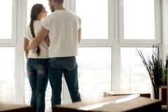 Jeunes couples embrassant en nouvel appartement avec les affaires emballées photographie stock