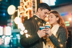 Jeunes couples embrassant et étreignant extérieur dans la rue de nuit au temps de Noël Photos stock