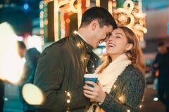 Jeunes couples embrassant et étreignant extérieur dans la rue de nuit au temps de Noël Images stock