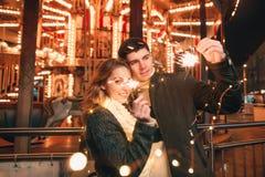 Jeunes couples embrassant et étreignant extérieur dans la rue de nuit au temps de Noël Photo stock
