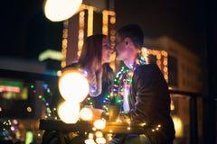 Jeunes couples embrassant et étreignant extérieur dans la rue de nuit au temps de Noël Photographie stock