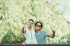 Jeunes couples embrassant et montrant des pouces dehors Photographie stock
