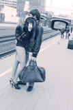 Jeunes couples embrassant sur la gare Images stock