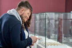 Jeunes couples en anneaux de achat d'amour au magasin de bijoux Image stock