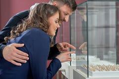 Jeunes couples en anneaux de achat d'amour au magasin de bijoux Photos libres de droits