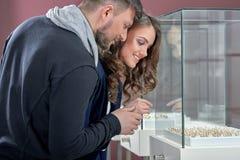 Jeunes couples en anneaux de achat d'amour au magasin de bijoux Photos stock