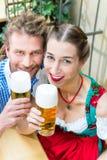 Jeunes couples en Bavière dans le restaurant ou le bar Images stock