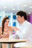 Jeunes couples en café n'agissant pas l'un sur l'autre mais au téléphone Image stock