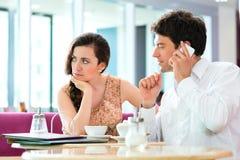Jeunes couples en café n'agissant pas l'un sur l'autre mais au téléphone photos libres de droits