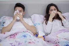 Jeunes couples en difficulté essuyant leur nez dans le lit image stock