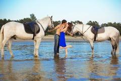 Jeunes couples en mer avec des chevaux Image libre de droits