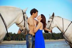 Jeunes couples en mer avec des chevaux Photographie stock
