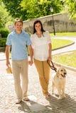 Jeunes couples en stationnement de marche de crabot d'amour Photographie stock libre de droits