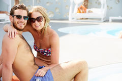 Jeunes couples en vacances détendant par la piscine Photos libres de droits