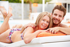 Jeunes couples en vacances détendant par la piscine Images stock