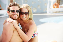 Jeunes couples en vacances détendant par la piscine Image stock