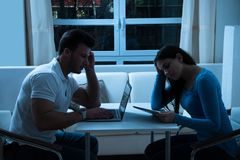 Jeunes couples ennuyés utilisant le comprimé numérique et l'ordinateur portable Photos libres de droits