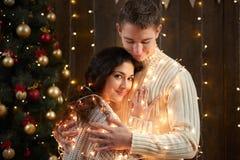 Jeunes couples ensemble dans les lumières et la décoration de Noël, habillées dans le blanc, arbre de sapin sur le fond en bois f Image libre de droits