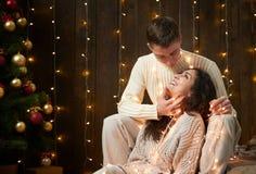 Jeunes couples ensemble dans les lumières et la décoration de Noël, habillées dans le blanc, arbre de sapin sur le fond en bois f Photographie stock libre de droits