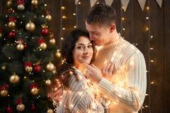 Jeunes couples ensemble dans les lumières et la décoration de Noël, habillées dans le blanc, arbre de sapin sur le fond en bois f Photos libres de droits