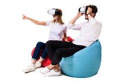 Jeunes couples enthousiastes éprouvant la réalité virtuelle posée sur des sacs à haricots d'isolement sur le fond blanc Image stock