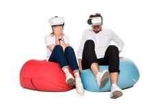 Jeunes couples enthousiastes éprouvant la réalité virtuelle posée sur des sacs à haricots d'isolement sur le fond blanc Images stock