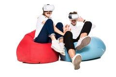 Jeunes couples enthousiastes éprouvant la réalité virtuelle posée sur des sacs à haricots d'isolement sur le fond blanc Image libre de droits
