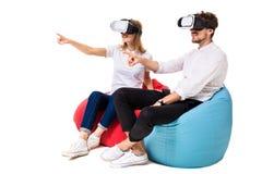 Jeunes couples enthousiastes éprouvant la réalité virtuelle posée sur des sacs à haricots d'isolement sur le fond blanc Photos libres de droits