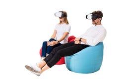 Jeunes couples enthousiastes éprouvant la réalité virtuelle posée sur des sacs à haricots d'isolement sur le fond blanc Photographie stock