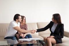 Jeunes couples enthousiastes et vraie poignée de main d'agent immobilier, successf Image libre de droits