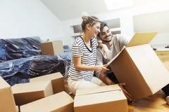 Jeunes couples entrant dans leur nouvelle maison Photos stock