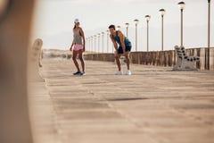 Jeunes couples environ à courir sur la promenade Image libre de droits