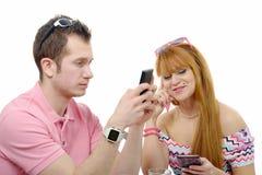 Jeunes couples envoyant des message textuels à leurs téléphones Images libres de droits