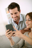 Jeunes couples envoyant le message court sur le smartphone de la maison Photo stock