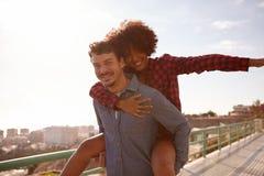 Jeunes couples espiègles jouant sur le dos Photographie stock