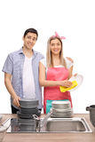 Jeunes couples essuyant des plats ensemble Photos stock