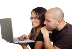 jeunes couples et ordinateur portatif de sourire Photo libre de droits