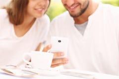 Jeunes couples et smartphone Images stock
