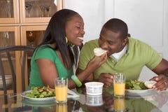 Jeunes couples ethniques par la table mangeant le déjeuner Images stock