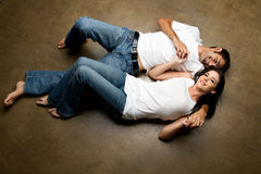 Jeunes couples ethniques sexy détendant sur l'étage Photo stock