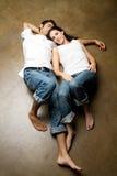 Jeunes couples ethniques sexy détendant sur l'étage Images libres de droits