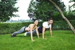 Jeunes couples exerçant et étirant des muscles avant acti de sport Photos stock