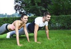 Jeunes couples exerçant et étirant des muscles avant acti de sport Photo stock