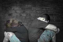 Jeunes couples fâchés contre l'un l'autre s'asseyant de nouveau au dos Photos stock