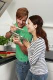 Jeunes couples faisant cuire dans la cuisine Images stock
