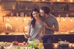 Jeunes couples faisant cuire dans la cuisine Photographie stock libre de droits
