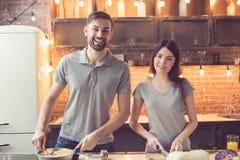 Jeunes couples faisant cuire dans la cuisine Image stock